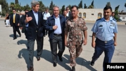 U.S. Secretary of State John Kerry (L) and Jordanian Foreign Minister Nasser Judeh (2nd L) are escorted by military officers to a helicopter bound for Zaatari refugee camp, at Marka airport in Amman, July 18, 2013.