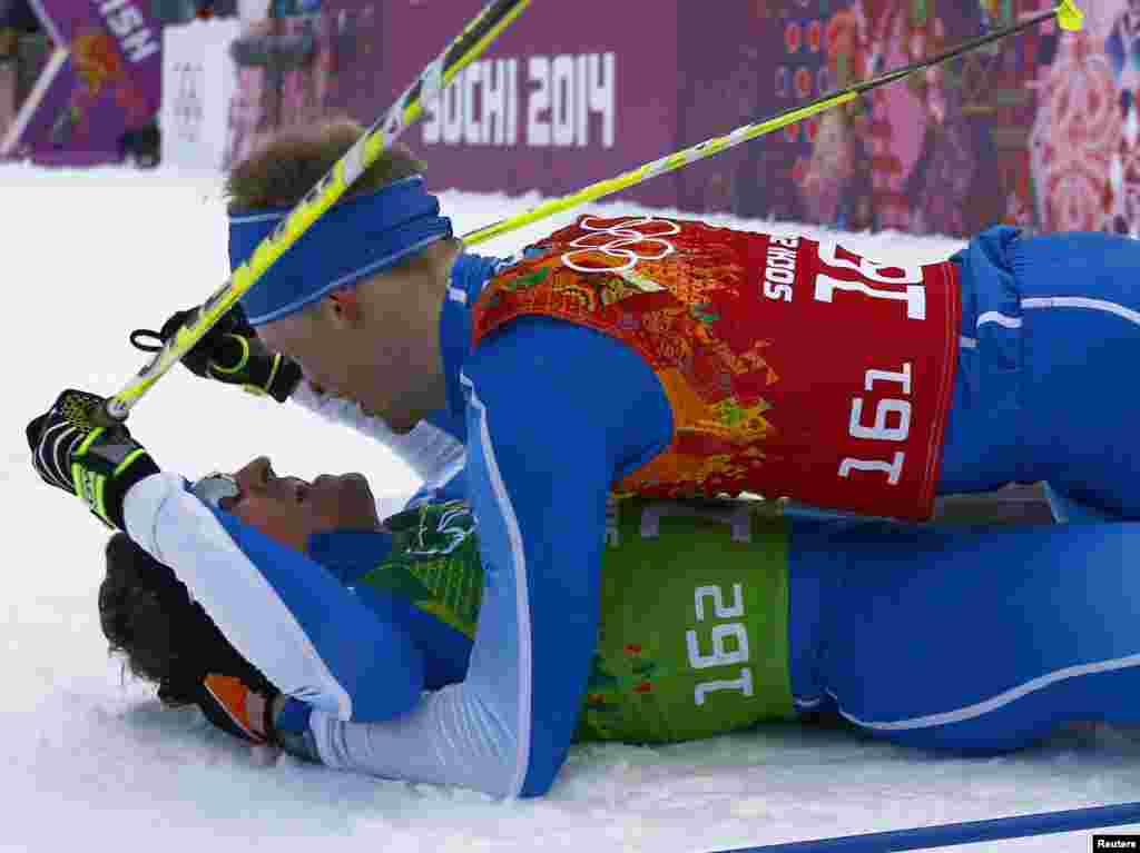 Finland's Sami Jauhojaervi and his team mate Finland's Iivo Niskanen (upper) celebrate after crossing the finish line in the men's cross-country team sprint classic fina, Sochi, Feb. 19, 2014.
