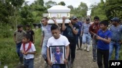 Un niño lleva una fotografía de la niña guatemalteca de 7 años, Jakelin Caal, quien murió en un hospital de Texas dos días después de ser detenida junto al padre por agentes de la patrulla fronteriza de EE.UU.