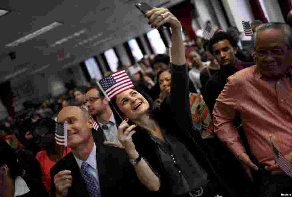A new U.S. citizen takes a selfie with her mobile phone after taking the Oath of Allegiance during a special naturalization ceremony at the U.S. Citizenship and Immigration Services District Office in the Manhattan borough of New York City.