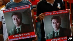 FILE - People carry portraits of student activist Nazimuddin Samad as they attend a rally to demand arrest of three motorcycle-riding assailants who hacked and shot Samad to death, in Dhaka, Bangladesh, April 8, 2016.