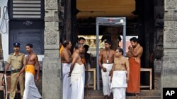 A policeman stands guard as temple staff crowd at the north side entrance of the 16th century Sree Padmanabhaswamy Temple in Trivandrum, India, July 6, 2011