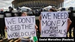 """Người biểu tình đứng trước cảnh sát chống bạo động bên ngoài sân vận động quốc gia Mane Garrincha tại Brasilia với các biểu ngữ: """"Chúng tôi không cần World Cup"""" """"Chúng tôi cần tiền cho các bệnh viện và giáo dục""""."""