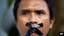 FILE - A Myanmar journalist with his mouth sealed with tape, symbolizing the government's recent crackdown on media, protest outside Myanmar Peace Center where President Thein Sein attends a meeting in Yangon, Myanmar, July 12, 2014.