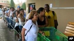 La gente en Puerto Rico hace fila en los supermercados en busca de alimentos no perecederos.