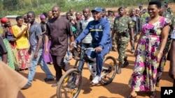 Pierre Nkurunziza, le président sortant du Burundi, se rend à vélo au bureau de vote, accopagné de sa femme et de ses partisans, dans son village natal de Ngozi, au Burundi, le 21 juillet 2015.