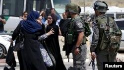 27일 무장한 팔레스타인 남녀가 사살된 요르단 서안지구 칼란디아 검문소 인근에서 한 팔레스타인 여성이 경찰과 실랑이를 벌이고 있다.