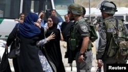 A Palestinian woman argues with an Israeli border policeman near the scene where two Palestinians where shot dead by Israeli forces near Qalandia checkpoint near the West Bank city of Ramallah, April 27, 2016.