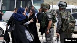 Seorang perempuan berdebat dengan polisi di dekat lokasi tertembaknya dua warga Palestina dekat pos penjagaan Qalandia, Ramallah, Tepi Barat (27/4).