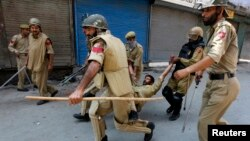 Polisi India membawa rekannya yang terluka dalam serangan di Srinagar, dekat wilayah Kashmir, 18 Juli 2013 (Foto: dok). Tentara India dilaporkan telah menewaskan 12 tersangka pemberontak di wilayah ini selama pertempuran lima hari yang berlangsung sejak Senin (29/7).