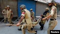کشمیر میں بھارتی سکیورٹی اہلکار اپنے زخمی ساتھ کو لے جاتے ہوئے (فائل فوٹو)