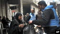 In this photo released by the Syrian official news agency SANA, a U.N relief worker, right, gives aid supplies to a Palestinian woman, at the gate of the besieged Yarmouk refugee camp, on the southern edge of the Syrian capital Damascus, Feb. 4, 2014.