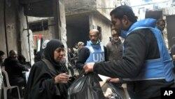지난 2월 유엔 직원들이 시리아 다마스쿠스 외곽 지역의 난민 캠프에서 구호물자를 나눠주고 있다.