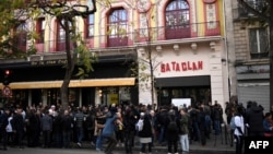 FILE - People stand in front of the Bataclan concert venue during ceremonies across Paris marking the second anniversary of the terror attacks of November 2015 in which 130 people were killed, in the French capital, Nov. 13, 2017. Rapper Medine's scheduled concerts at the Bataclan have caused controversy.