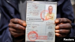 An African migrant shows his ID at a detention center in Zawiya, northern Libya, May 27, 2014.