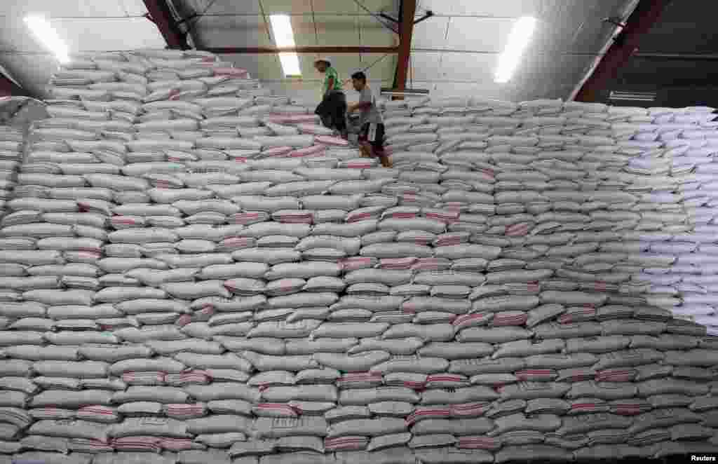 National Food Authority workers walk atop sacks of rice as they make an inventory of rice stocks at a government rice warehouse in Taguig, Metro Manila, Philippines.