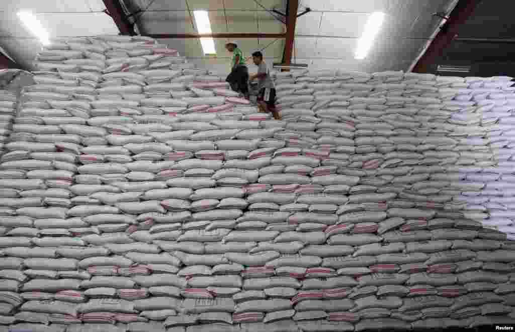 필리핀 마닐라의 정부 곡물 창고에 쌀 부대 자루들이 쌓여있다. 그 위를 직원들이 걸어다니고 있다.