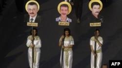 Les filles coptes égyptiennes portent des photos de certaines des victimes qui ont été tuées dans des affrontements avec les militaires, lors d'une procession de deuil en Egypte, 11 novembre 2011.
