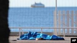 Cuerpos de víctimas cubiertos por mantas a la orilla del Mediterráneo, en Niza.