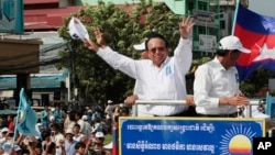 FILE - In this June 2, 2017, file photo, opposition party Cambodia National Rescue Party (CNRP) leader Kem Sokha greets his supporters at a rally in Phnom Penh. The European Union said Tuesday it has suspended assistance to Cambodia's election commission following last month's dissolution of the country's main opposition party and warned that next July's general election will not be legitimate if the opposition is not allowed to participate. (AP Photo/Heng Sinith, File)