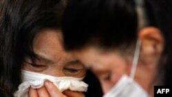 Minako Oikawa (trái) khóc khi gặp người thân tại trung tâm di tản gần khu vực bị tàn phá ở Rikuzentakata, miền bắc Nhật Bản