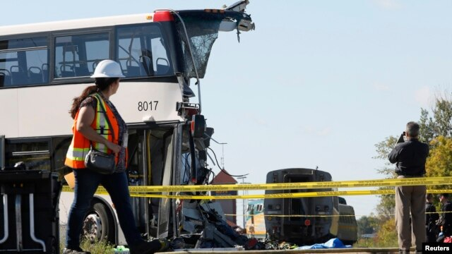 An official takes pictures at the scene of the accident involving a bus and a train, Ottawa, September 18, 2013.