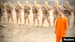A man purported to be Islamic State captive Jordanian pilot Muath al-Kasaesbeh (in orange jumpsuit) stands in front of armed men in this still image from an undated video filmed from an undisclosed location made available on social media on February 3, 20