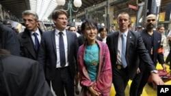Aung San Suu Kyi (tengah) saat tiba di stasiun kereta api Gare du Nord di Paris, Selasa (26/6).