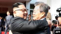 This picture taken on May 26, 2018 and released by the Blue House via Dong-A Ilbo shows South Korea's President Moon Jae-in (R) hugging North Korea's leader Kim Jong Un after their second summit at the north side of the truce village of Panmunjom.