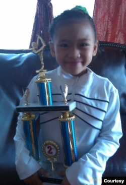 Sunisa Lee, at the age of 7, with her first trophy. (Courtesy of Lee's family)