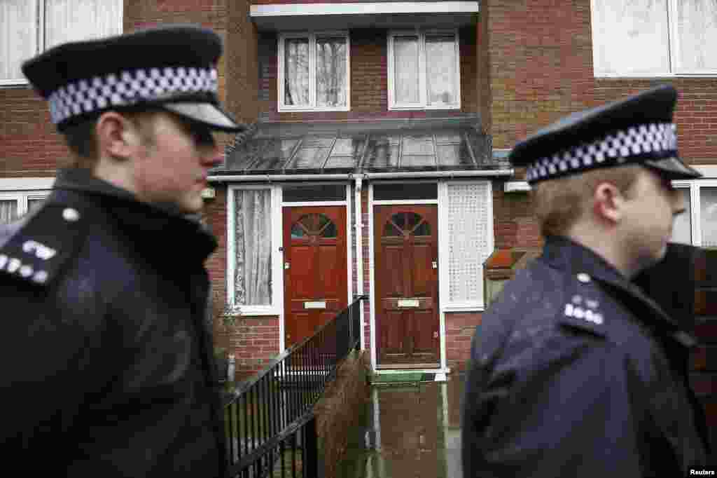 "Two police officers walk outside a flat in London, February 26, 2015. Local media reported that the flat is the former home of Mohammed Emwazi, whom investigators believe is the ""Jihadi John"" masked fighter who fronted the Islamic State militant beheading videos."