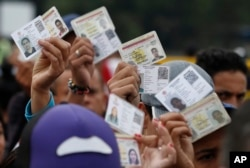 FILE - Venezuelan citizens hold up their identification cards for inspection by the Colombian immigration police, in Cucuta, Colombia, on the border with Venezuela, Feb. 22, 2018.