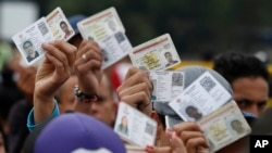 Venezuelan citizens hold up their identification cards for inspection by the Colombian immigration police, in Cucuta, Colombia. (File)