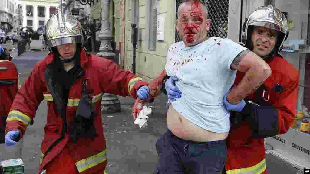 Un homme est emmené par des secouristes après avoir été blessé lors d'affrontements après le match, le 11 juin 2016.