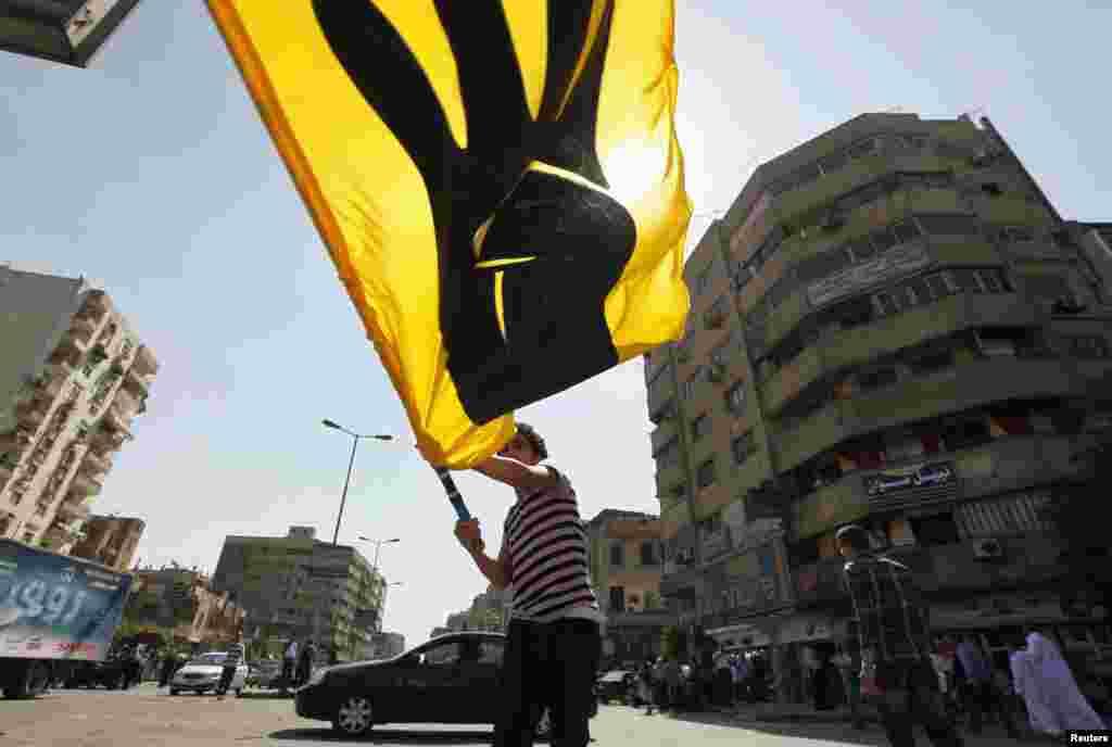 埃及被推翻的总统穆尔西的支持者10月4日在开罗的游行中挥舞一面旗帜。