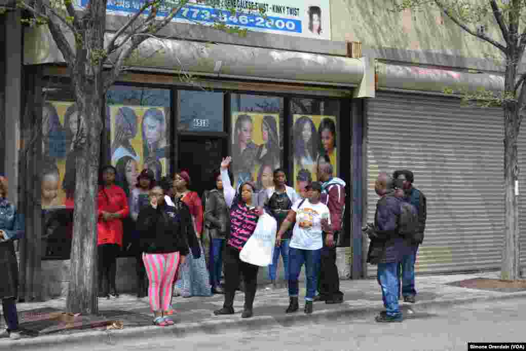 Women step out of a neighborhood hair salon to cheer on participants of a prayer walk marching for peace in their neighborhood, Englewood, on Chicago's South Side, April 14,2017. The area is regularly hit with gun violence.