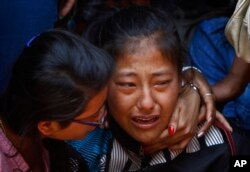 FILE - A relative of one of the Nepalese climbers killed in an avalanche on Mount Everest cries during the funeral ceremony in Katmandu, Nepal, April 21, 2014.