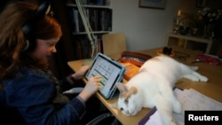 Alice Wilkinson is joined by her cat Freddie as she does her maths online schooling amid the outbreak of COVID-19 in Manchester, Britain, January 15, 2021. REUTERS