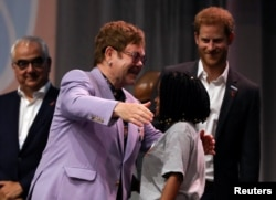 "British musician Elton John embraces a participant as Britain's Prince Harry looks on during a panel ""Breaking barriers of inequity in the HIV response"" during the 22nd International AIDS Conference (AIDS 2018), the largest HIV/AIDS-focused meeting in the world, in Amsterdam, Netherlands, July 24, 2018."