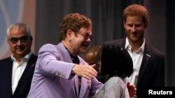 """El músico británico Elton John abraza a un participante mientras el príncipe Harry ve durante un panel """"Rompiendo barreras de inequidad en la respuesta al VIH"""" durante la 22ª Conferencia Internacional de SIDA (AIDS 2018), en Amsterdam, Países Bajos, 24 de julio de 2018."""