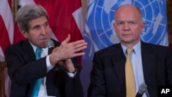 British Foreign Secretary William Hague listens at right as Secretary of State John Kerry speaks at the State Department in Washington, Tuesday, Feb. 25, 2014, during a discussion on ending sexual violence and conflict in war.