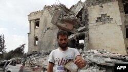 一个叙利亚人向人们展示从空袭废墟中找到的一片纸。2014年9月25日,以美国为主导的联盟向与基地组织有联系的叙利亚努斯拉总部实施了空袭。