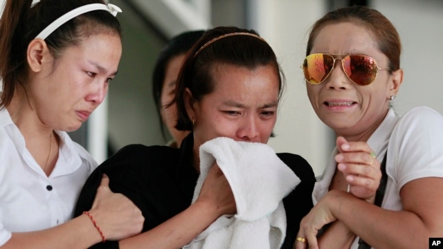 Noppawan Chairat, center, the mother of two children killed in Sunday's bomb attack on an anti-government protest site, Noppawan Chairat, is held by her family members as they wait for their bodies at a hospital in Bangkok, Thailand, Monday, Feb. 24, 2014