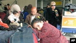 Passengers wait under large tent set-up in the parking lot outside Cairo's International airport as Egyptians and foreigners prepare to leave Egypt, February 1, 2011