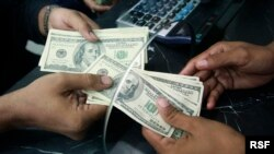 A Pakistani currency dealer counts U.S. dollar notes at his shop in Karachi October 23, 2008. Pakistan has not formally asked for a facility from the International Monetary Fund (IMF), the prime minister's top adviser on economic affairs said on Thursday,