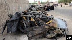 ພົນລະເຮືອນຈຳນວນນຶ່ງ ພາກັນໄປຫຸ້ມເບິ່ງ ບ່ອນໂຈມຕີ ໂດຍລະເບີດລົດ ທີ່ເຫຼືອແຕ່ຊາກລົດລະເບີດ ໃນເຂດຄຸ້ມ Shula ຂອງນະຄອນຫລວງ Baghdad ປະເທດ Iraq, ວັນທີ 12 ຕຸລາ 2014.