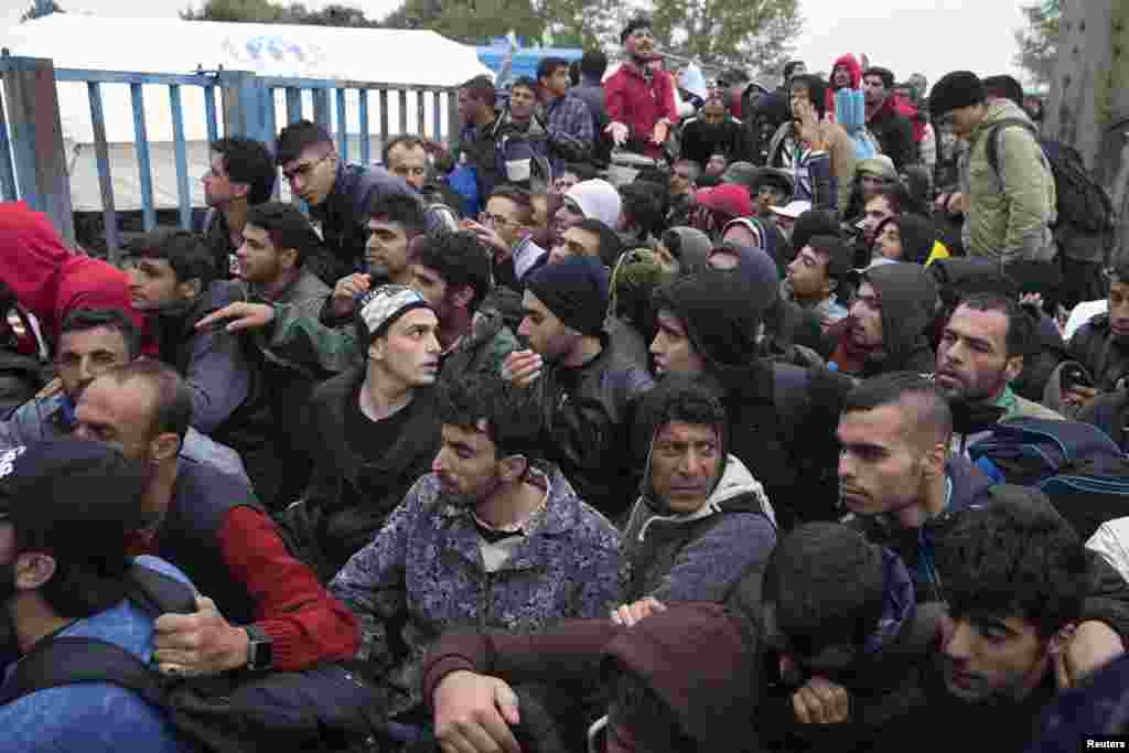 Migrants wait in front of a registration camp for migrants in Opatovac, Croatia. Interior Minister Ranko Ostojic said Croatia will demand that Greece stop moving migrants from the Middle East on to the rest of Europe. Around 29,000 people, mostly from Syria, have arrived in Croatia from Serbia in the past week after trekking northwards through the Balkans from Greece.