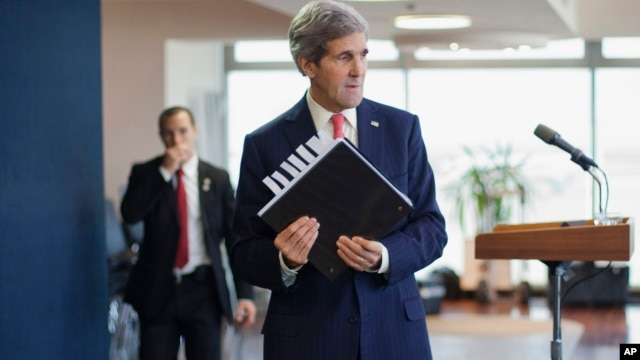 U.S. Secretary of State John Kerry picks up his notebook after answering questions from members of the media before his departure from Ben Gurion International Airport in Tel Aviv, Dec. 6, 2013.
