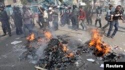 مشتعل مظاہرین نے سڑک پر آگ لگائی ہوئی ہے