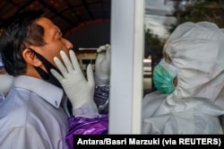 Petugas medis mengambil sampel usap dari seorang petugas untuk mencegah penyebaran Covid-19 di Palu, Provinsi Sulawesi Tengah, 3 Juni 2020. (Foto: Antara/Basri Marzuki via REUTERS)